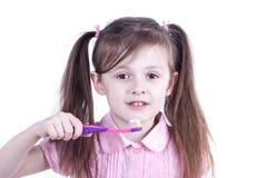 Chica joven que aplica sus dientes con brocha Imagen de archivo libre de regalías