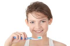 Chica joven que aplica sus dientes con brocha feliz Fotografía de archivo libre de regalías