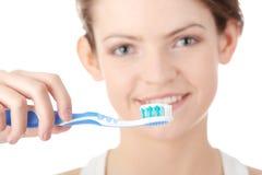 Chica joven que aplica sus dientes con brocha feliz Imagen de archivo libre de regalías