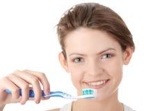 Chica joven que aplica sus dientes con brocha feliz Imagenes de archivo