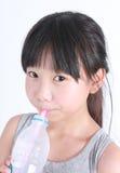 Chica joven que bebe el agua dulce de una botella Imagen de archivo