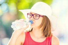 Chica joven que bebe el agua dulce en un día de verano caliente Imágenes de archivo libres de regalías