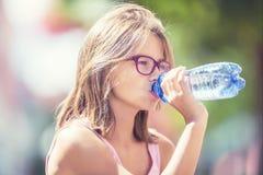 Chica joven que bebe el agua dulce en un día de verano caliente Fotografía de archivo