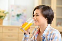 Chica joven que bebe el zumo de naranja Fotos de archivo