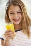 Chica joven que bebe el zumo de naranja Imagen de archivo libre de regalías