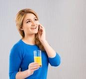 Chica joven que bebe el zumo de naranja y que habla en un teléfono Foto de archivo