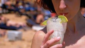 Chica joven que bebe un cóctel exótico del tubo en el verano en la playa almacen de video