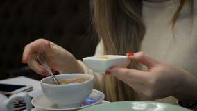 Chica joven que bebe una taza de té en el restaurante almacen de video