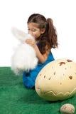 Chica joven que besa su conejito del juguete foto de archivo