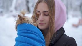 Chica joven que besa a un terrier de Yorkshire en un parque nevado del invierno que sostiene un perro envuelto en una manta azul  metrajes