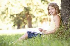 Chica joven que bosqueja en el campo que se inclina contra árbol Fotografía de archivo