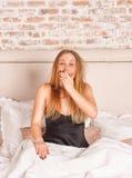 Chica joven que bosteza en cama Imágenes de archivo libres de regalías