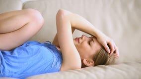 Chica joven que cae en el sofá, sintiendo presionado, teniendo dolor de cabeza fuerte almacen de metraje de vídeo