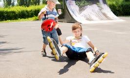 Chica joven que cae mientras que patina Imágenes de archivo libres de regalías