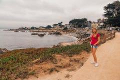 Chica joven que camina abajo de la costa costa en Monterey Foto de archivo libre de regalías