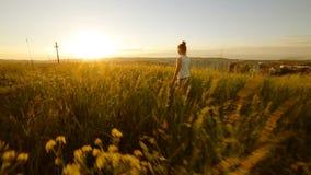 Chica joven que camina en el campo para cruzar en puesta del sol almacen de metraje de vídeo