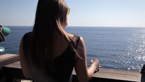 Chica joven que camina en la terraza de su sitio con una opinión del mar metrajes