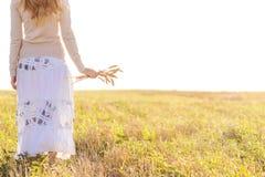 Chica joven que camina en un campo con los oídos en la mano Imágenes de archivo libres de regalías