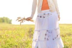Chica joven que camina en un campo con los oídos en la mano Fotografía de archivo libre de regalías