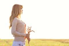 Chica joven que camina en un campo con los oídos en la mano Imagenes de archivo