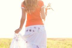 Chica joven que camina en un campo con los oídos en la mano Imagen de archivo libre de regalías