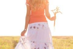 Chica joven que camina en un campo con los oídos en la mano Fotos de archivo libres de regalías