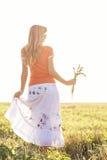 Chica joven que camina en un campo con los oídos en la mano Imagen de archivo