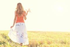 Chica joven que camina en un campo con los oídos en la mano Foto de archivo libre de regalías