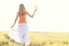 Chica joven que camina en un campo con los oídos en la mano Fotos de archivo
