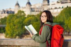 Chica joven que camina a lo largo del Sena con el mapa de París Imagen de archivo