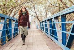 Chica joven que camina sobre el puente en primavera temprana Fotografía de archivo