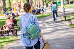 Chica joven que camina a través de un parque de la ciudad foto de archivo