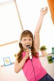 Chica joven que canta con la mano encima del colmo Foto de archivo libre de regalías