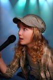 Chica joven que canta con un micrófono en la etapa Foto de archivo libre de regalías