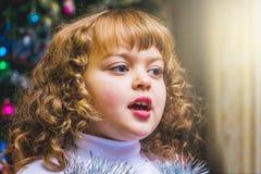 Chica joven que canta en el ` s Eve del Año Nuevo en el fondo borroso Cristo Imagenes de archivo