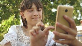 Chica joven que charla en una tableta con los amigos la muchacha hermosa escribe en smartphone una letra en parque en la primaver metrajes