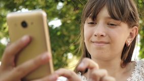 Chica joven que charla en una tableta con los amigos la muchacha hermosa escribe en smartphone una letra en parque en la primaver almacen de metraje de vídeo