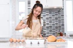 Chica joven que cocina el concepto del pan de la panadería, haciendo la torta con el huevo imagen de archivo libre de regalías