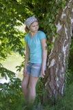 Chica joven que coloca el árbol de abedul cercano Foto de archivo