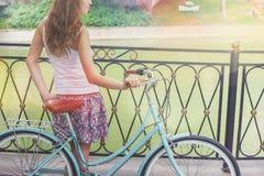 Chica joven que coloca la cerca cercana cerca de la bici del vintage en el parque Foto de archivo libre de regalías