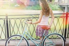 Chica joven que coloca la cerca cercana cerca de la bici del vintage en el parque Foto de archivo