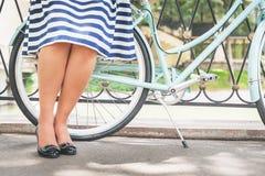 Chica joven que coloca la cerca cercana cerca de la bici del vintage en el parque Fotos de archivo