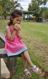 Chica joven que come Apple en el patio Fotos de archivo