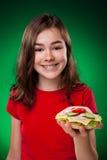 Chica joven que come el emparedado grande Imagen de archivo