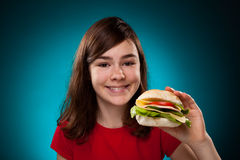 Chica joven que come el emparedado grande Imagen de archivo libre de regalías