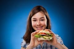 Chica joven que come el emparedado grande Imagenes de archivo