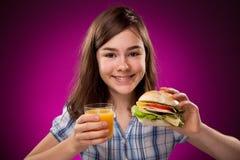 Chica joven que come el emparedado grande Fotos de archivo