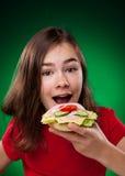 Chica joven que come el emparedado grande Fotos de archivo libres de regalías