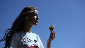 Chica joven que come el helado al aire libre en verano, en calor almacen de metraje de vídeo