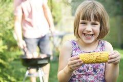 Chica joven que come el maíz dulce en la barbacoa de la familia Imágenes de archivo libres de regalías